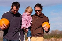 Parents and daughter carrying pumpkins