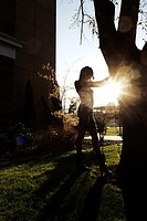 A young woman standing by a tree, backlit by the sun