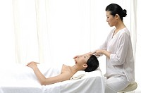 Young woman getting face massage from a massage therapist (thumbnail)