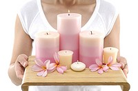 Close_up of a woman holding lit candles and flowers