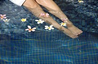 Woman putting her legs in a swimming pool
