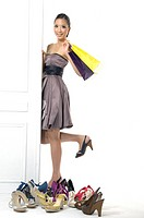 Woman standing beside a door near a collection of footwear and holding shopping bags