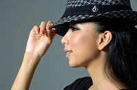 Close_up of a fashion model holding her hat