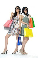 Women carrying shopping bags and smirking