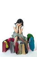 Woman depressed while looking at clothes near shopping bags (thumbnail)