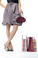 Woman holding a purse and standing near shopping bags