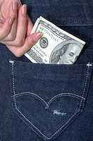 Woman putting US dollar bill in her jeans pocket