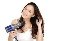 Portrait of young woman using a hair dryer