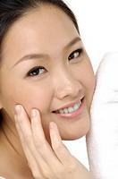 young beautiful woman with cotton swab cleaning her face