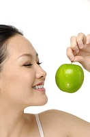 Beautiful smiling Asian woman with green apple