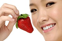 portrait on isolated background of a young beautiful asian woman eating a strawberry