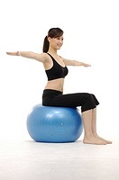 young woman practicing yoga on exercise ball