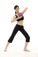 Young woman practicing yoga with ball (thumbnail)