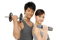 young couple lifting dumbbells on white