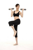 young woman using dumbbell weights, posing in studio, portrait