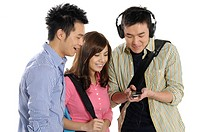University students looking at an mp3 player held by their friend