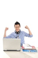 Male university student with his arms raised in front of a laptop