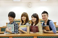 University students holding books and smiling in a classroom (thumbnail)