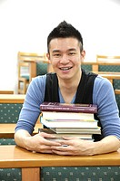 Male university student sitting with a stack of books in a classroom
