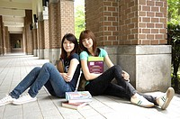 Female university students sitting back to back and smiling