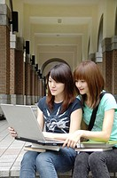 Female university students using a laptop in the corridor