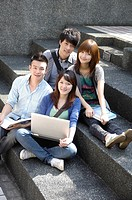 University students sitting together on steps and smiling