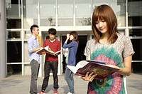 Female university students reading a book with friends standing behind him