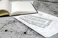 Close_up of blueprints and diary in an office