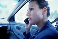 Side profile of a businesswoman talking on a mobile phone in a car