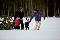 Parents walking on snow with their son and daughter