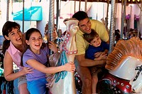 Parents with their son and daughter riding on carousel horses