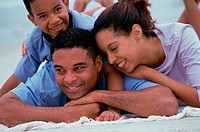 Close_up of parents smiling with their son on the beach