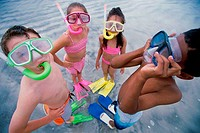 High angle view of two boys and two girls wearing snorkel masks and flippers on the beach