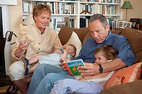 Mature couple sitting on a couch with their grandson and granddaughter
