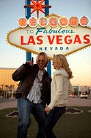 Young couple dancing in front of a welcome sign, Las Vegas, Nevada, USA