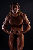 Athletic sexy male body builder with the blonde long hair. on black background