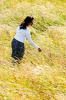 Woman strolling through tall grass