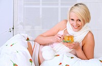 Blond woman drinking tea in bed