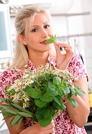 Blond woman smelling at chamomile leaf, portrait
