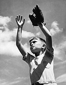 Low angle view of a boy wearing a baseball glove with his arms raised