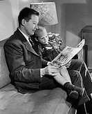 Father reading a book with his son sitting on his lap