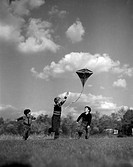 Vintage photograph of children playing with kite