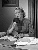 Woman sitting at desk holding booklet