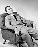 Businessman reclining in an armchair