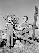 Boy and girl with pumpkins on farm