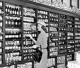 Side profile of a mid adult woman picking bottle from a shelf in a store