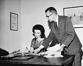 Businesswoman checking documents with a businessman standing beside her