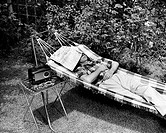 Man relaxing in hammock listening to radio