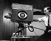 Side profile of a cameraman shooting in a television studio