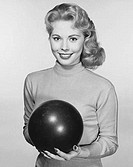 Young woman holding a bowling ball and smiling